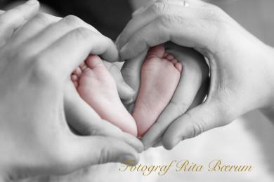 Foreldrene holder hendene rundt de små barneføttene og danner et hjerte
